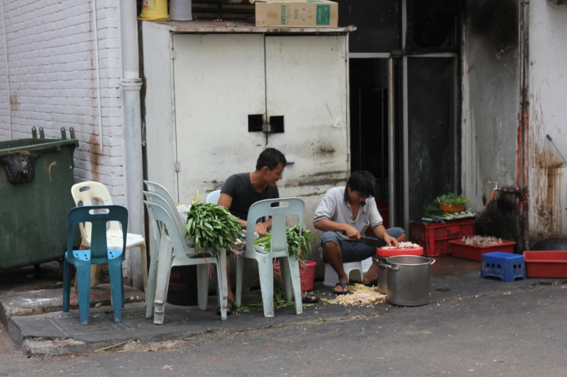 Can you see what the guy on the left is up to? He's chopping the nails off chicken feet (I think). That's what the pile on the ground is.